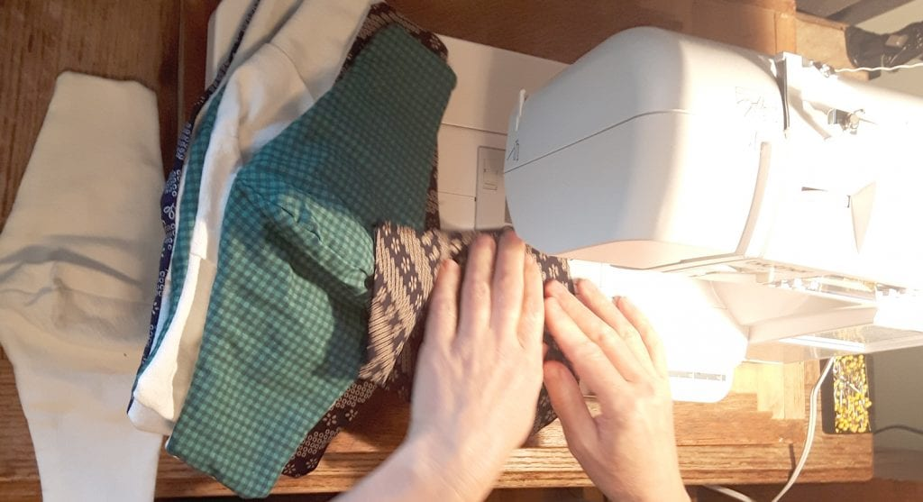 Sewing machine with hands at base and several face masks