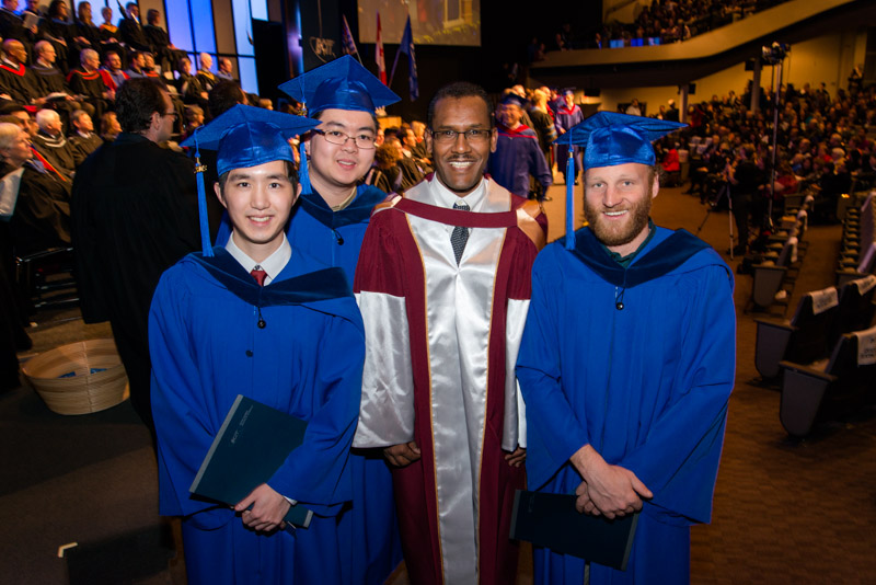photo of three student graduates with faculty
