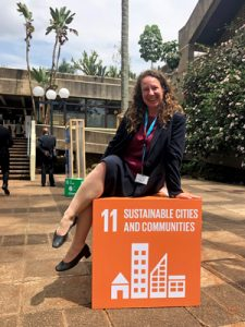 Image of Jennie Moore sitting on the Sustainable Development Goal 11 cube for Sustainable Cities and Communities.