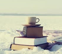 A pile of books on a field of snow with a coffee cup balanced on top.