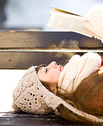 Woman laying on bench wearing winter clothes, reading a book in cold weather.