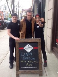 Liam Neeson poses with staff of the Big Star Sandwich Company.