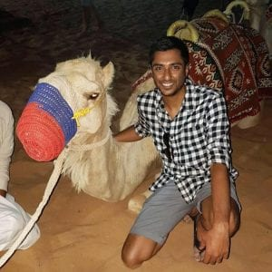 BCIT student Tabrez Hussein on a recent trip to Dubai, posing beside a camel.