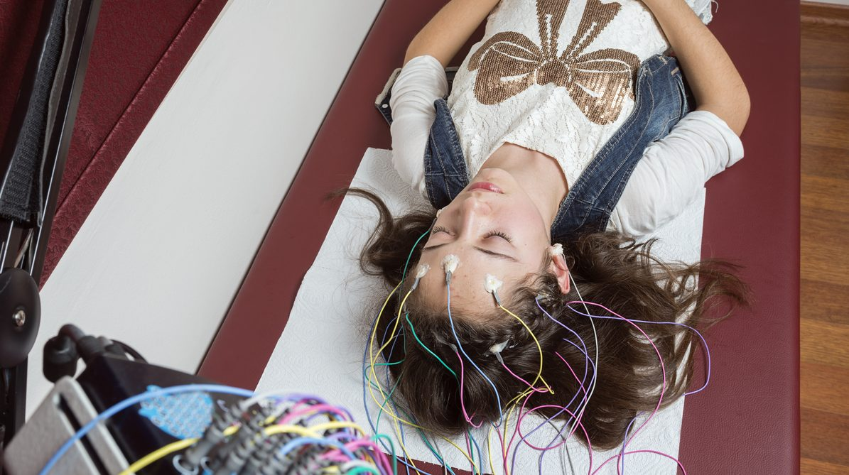 Girl connecting to electroencephalography apparatus, with diodes attached to her head as she lies on a hospital bed.