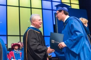 David Emerson shakes hands with graduate.