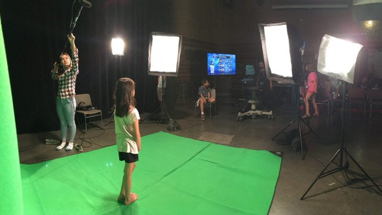 A girl stands on a green screen backdrop at broadcast camp while another girl holds a boom mic