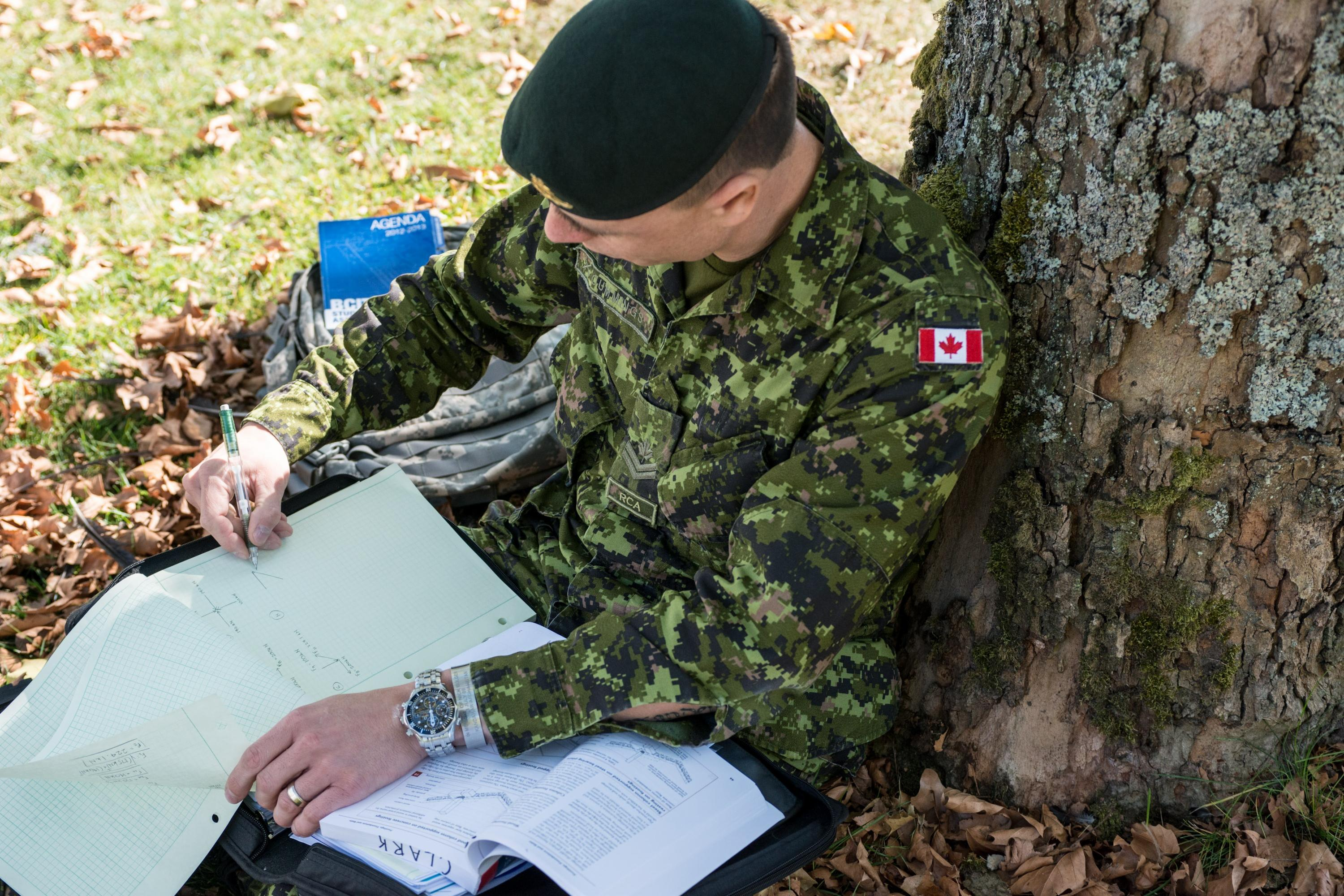 Legion Military Skills Conversion program man sits under tree at BCIT wearing uniform and studying books.