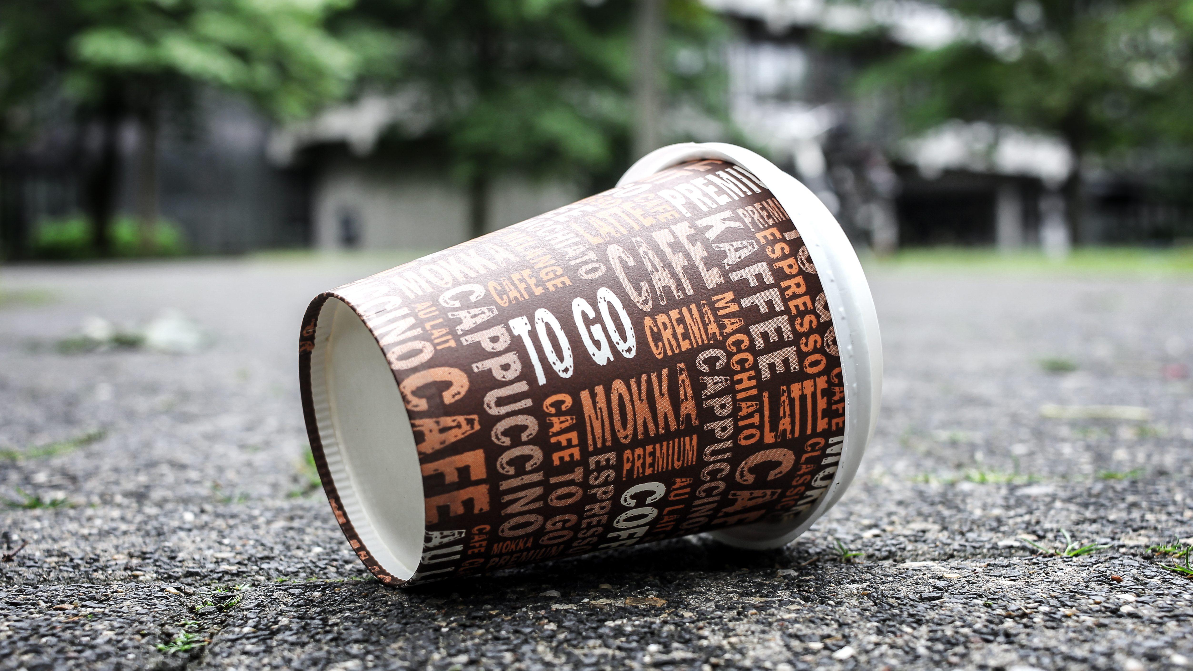 Used Coffee mug at sidewalk as symbol for pollution