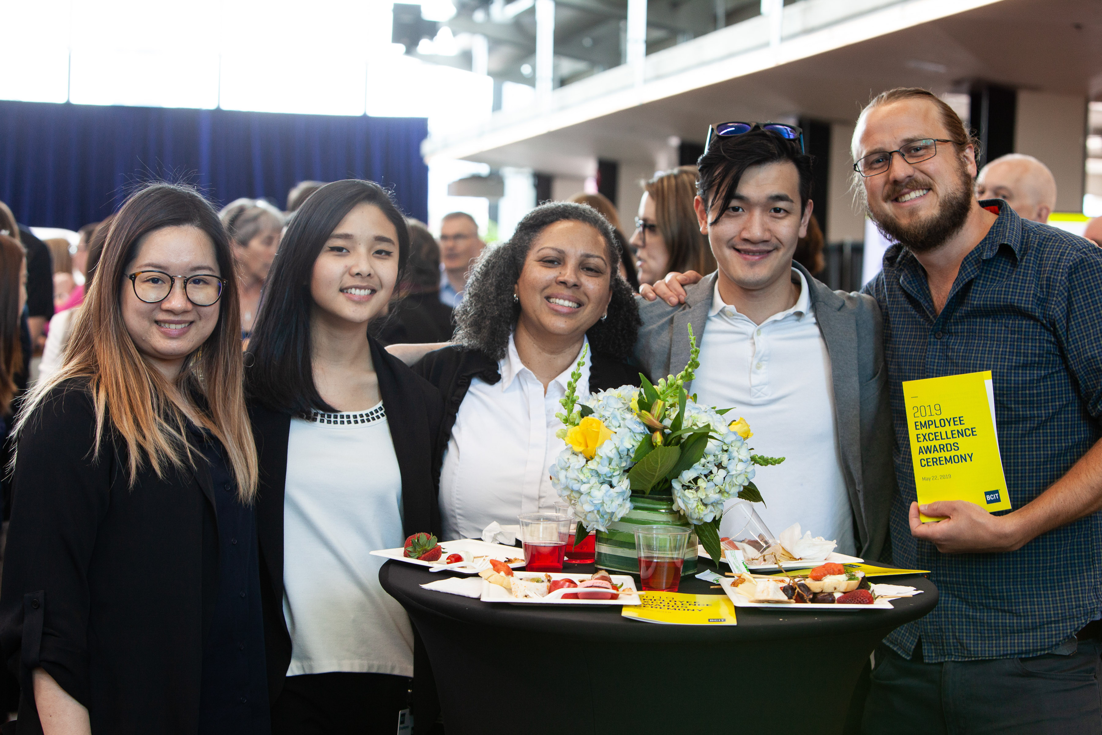 Five BCIT employees stand together in front of a table of flowers at the 2019 BCIT Employee Excellence awards.