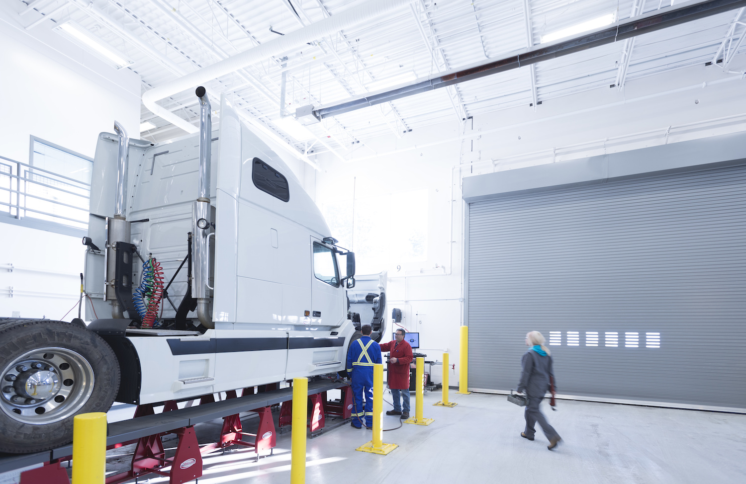 large white truck in a large clean white warehouse with 2 employees working on the engine