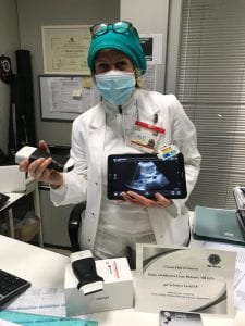 Healthcare worker in Italy wearing a surgical mask holds a Clarius wireless ultrasound device and a tablet with an ultrasound image displayed on it.