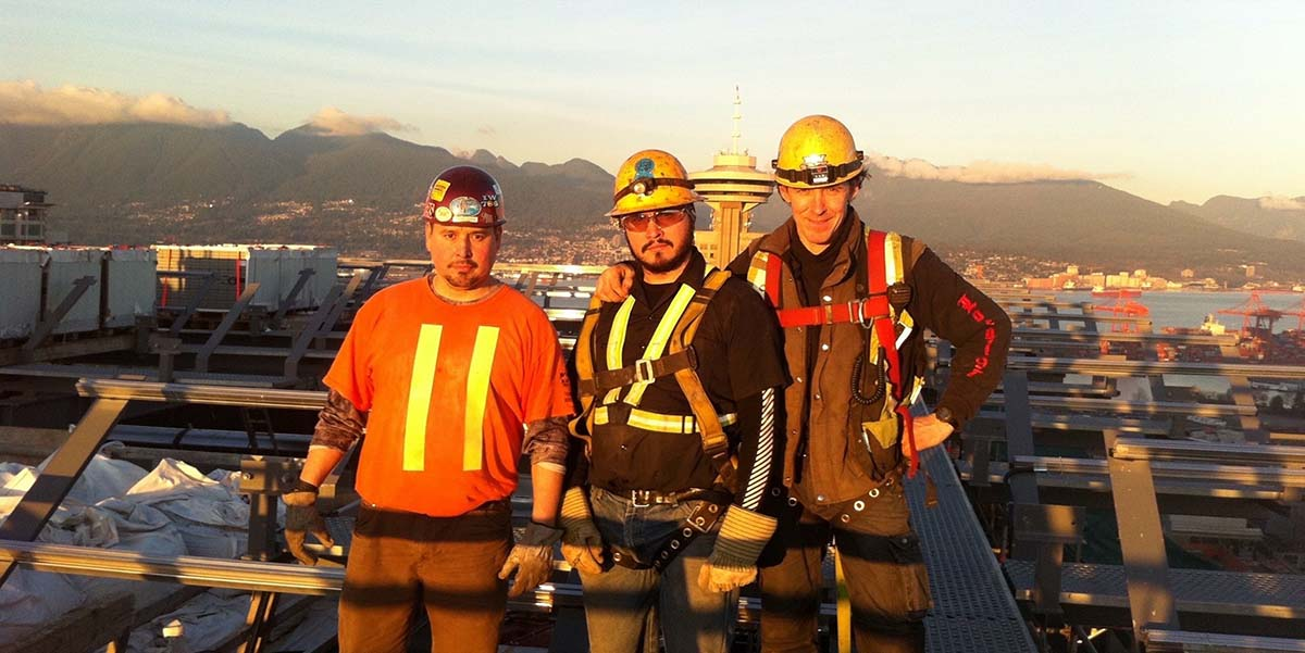 BCIT Indigenous alumnus Brandon Darbyshire-Joseph stands at a job site with two co-workers