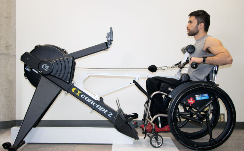 Man seated at wheelchair using a rowing ergometer