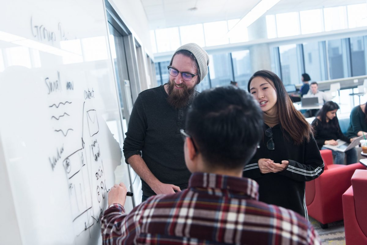 Three students use white board to plan website architecture