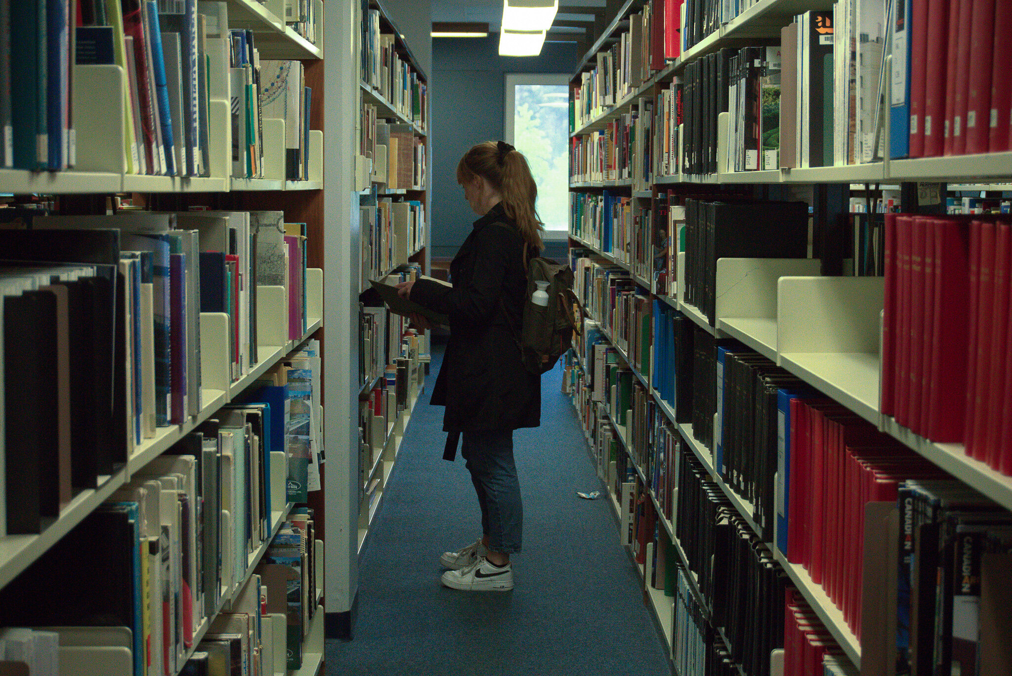 Student in library looking at books on the shelf
