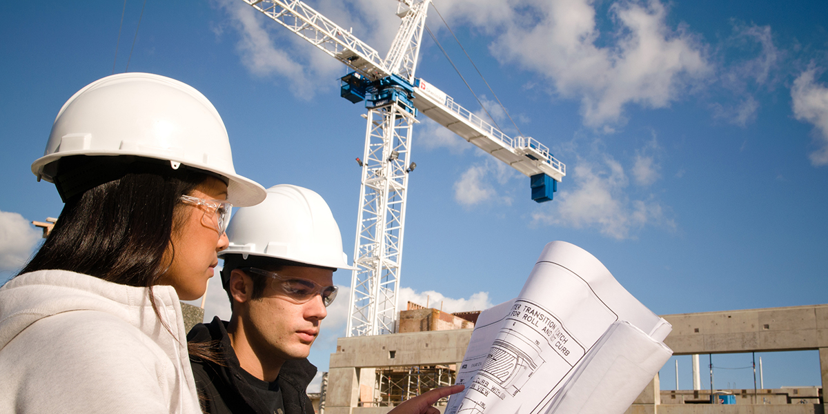 Woman and man wearing white construction hats, looking at blueprints, in front of a crane.