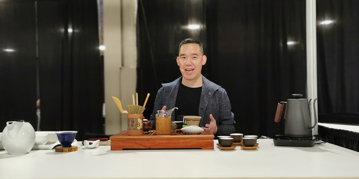 Matt Chong sits at a table with tea tasting cups and a kettle