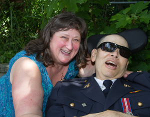 woman in blue dress smiles next to a man in uniform with sunglasses and a big smile