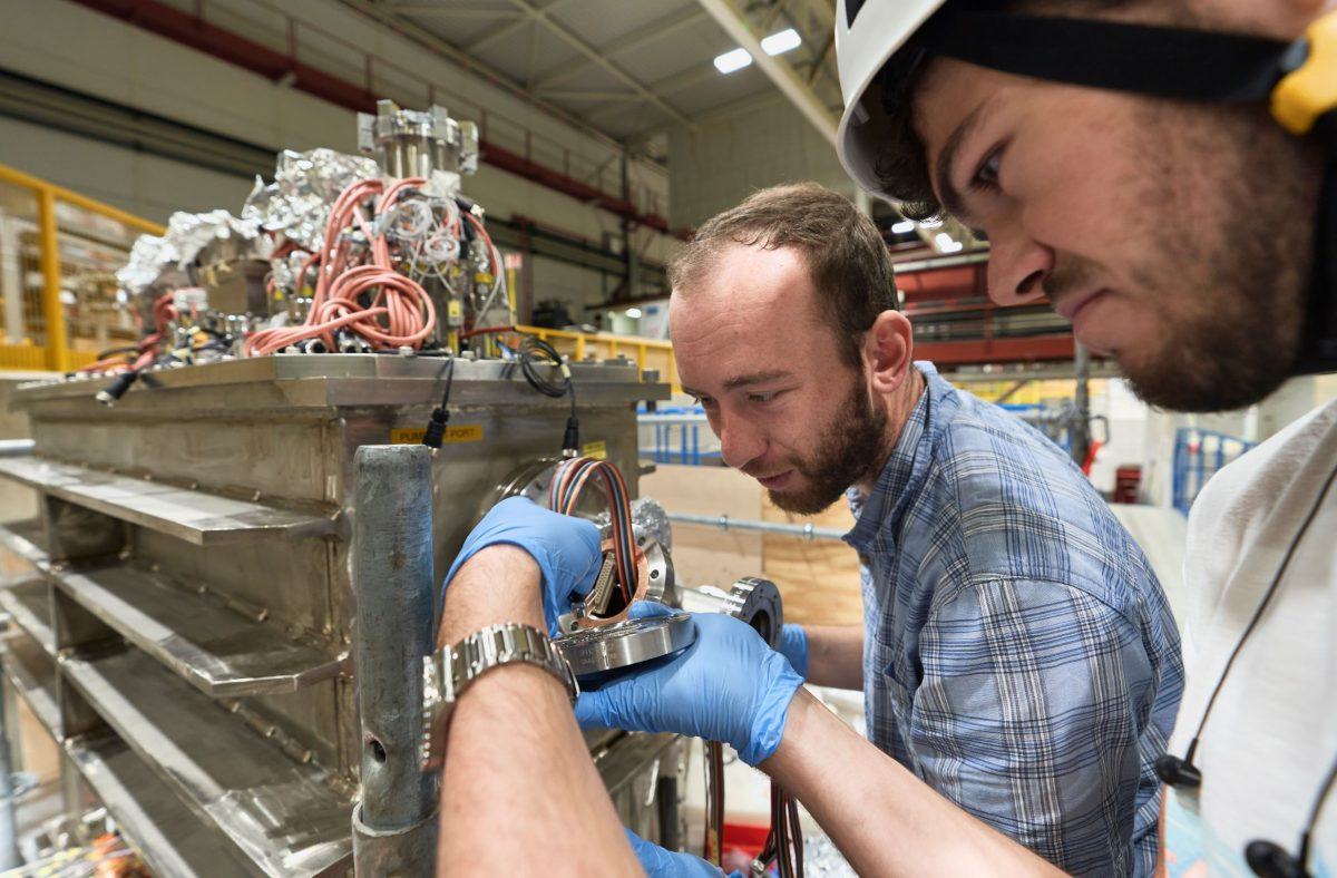 Two researchers looking at complex metal device with many wires