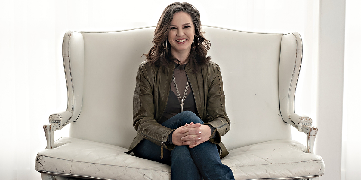 Brandy Kawulka sits on a white loveseat smiling at the camera with hands crossed in front of her