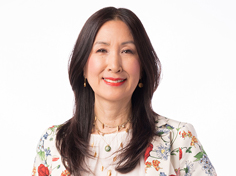 Carol Lee with long dark hair smiles to camera in floral suit