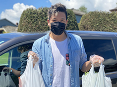 Karl Chen poses with two bags of groceries in a mask