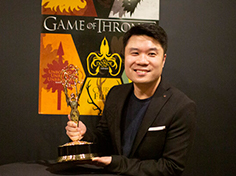 Mark Wong smiles in suit holding Emmy award in front of Game of Thrones poster