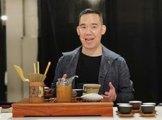 Matt Chong smiles in front of tea tasting display