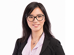 Michelle Wan smiles in glasses and a blazer