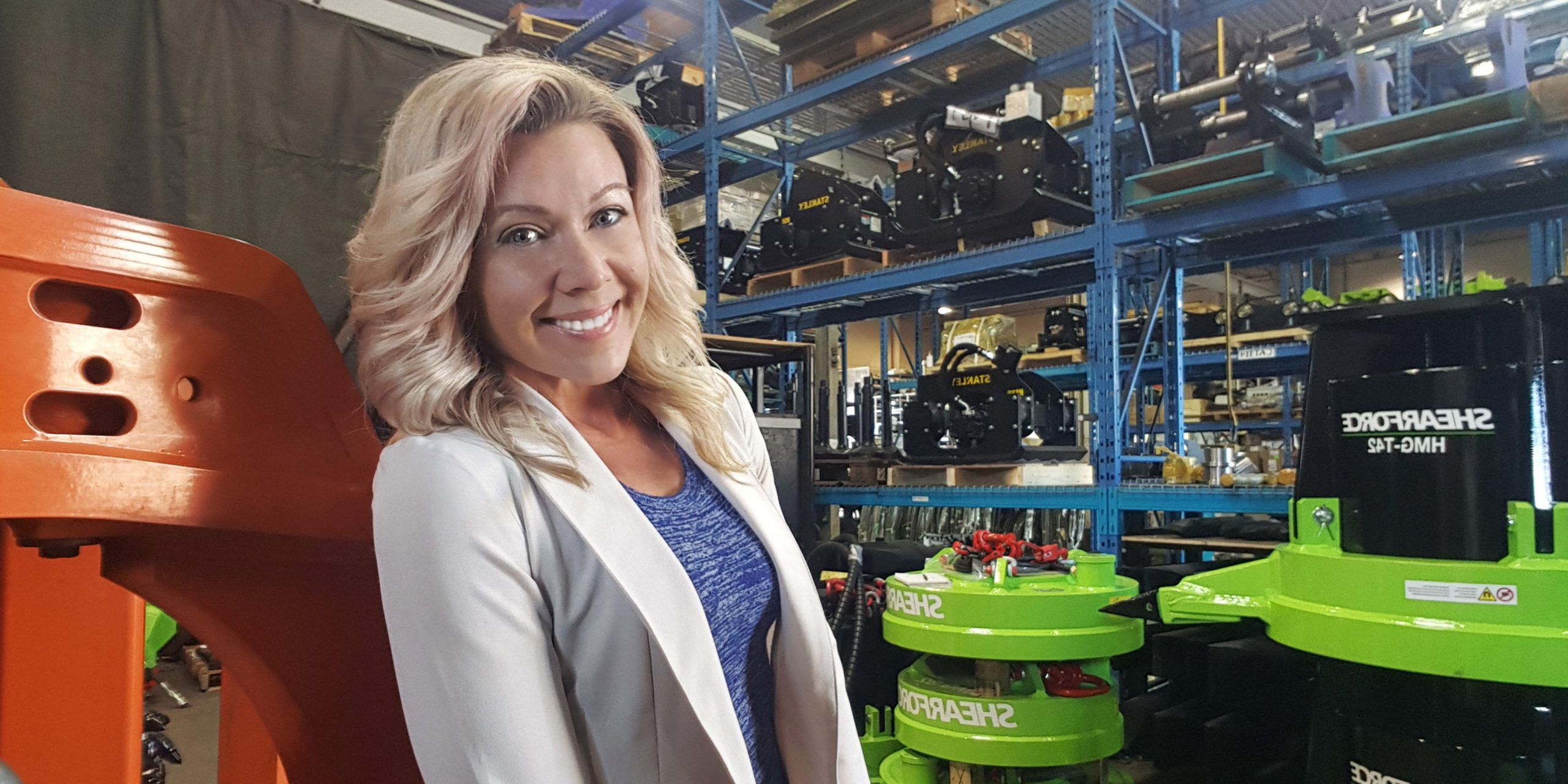 A blonde woman stands in a warehouse smiling.