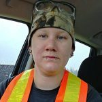 Female Indigenous welding alumna wearing safety vest and hat