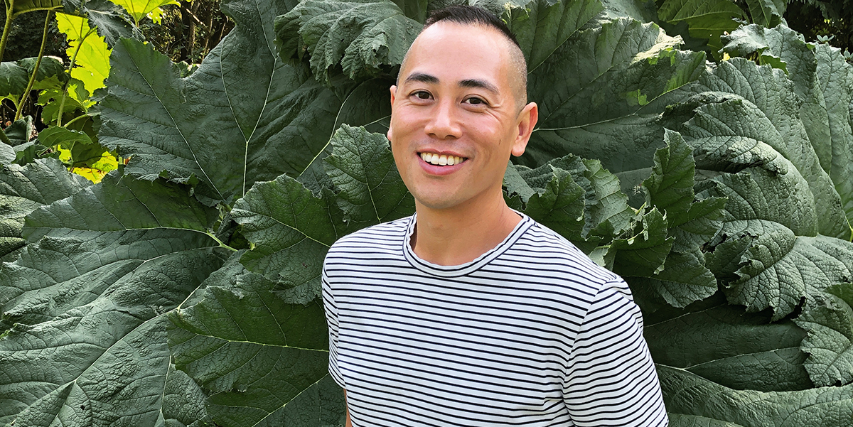 Eddy Boudel Tan smiling in striped t-shirt against backdrop of greenery