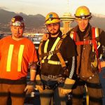 Male Indigenous ironworker alumnus wearing safety vest and hard hat standing with two other men