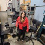 Indigenous female machinist alumna standing in machine shop
