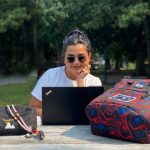 Indigenous female broadcast journalism alum sitting at a picnic table in a park with laptop wearing sunglasses