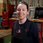 Indigenous female machinist alum and faculty member standing in machine shop smiling