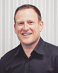 Joe Geluch smiling in black shirt for the BCIT alumni-owned business article