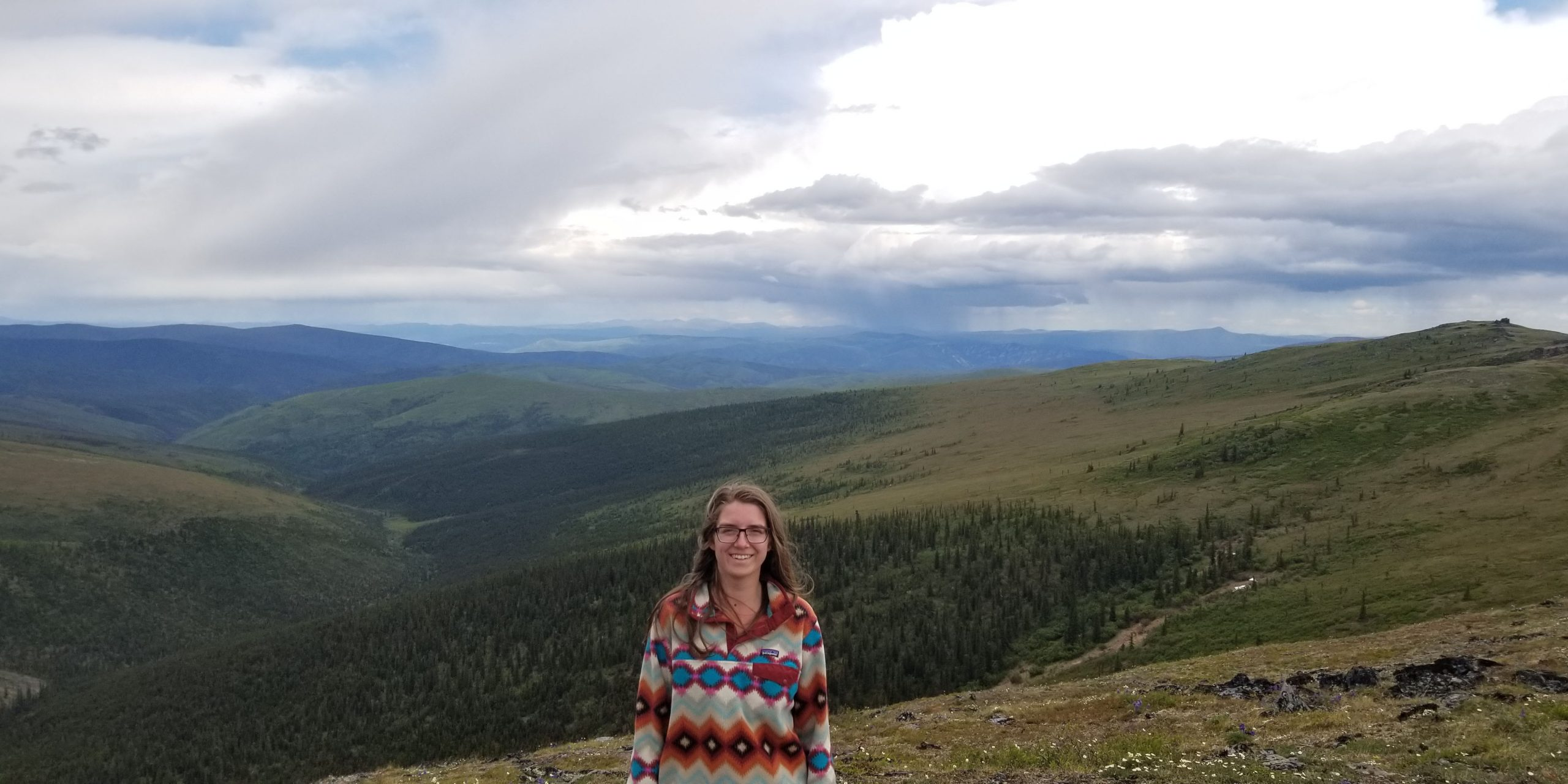 A female student with shoulder length brown hair posing in front of a mountain range, smiling.