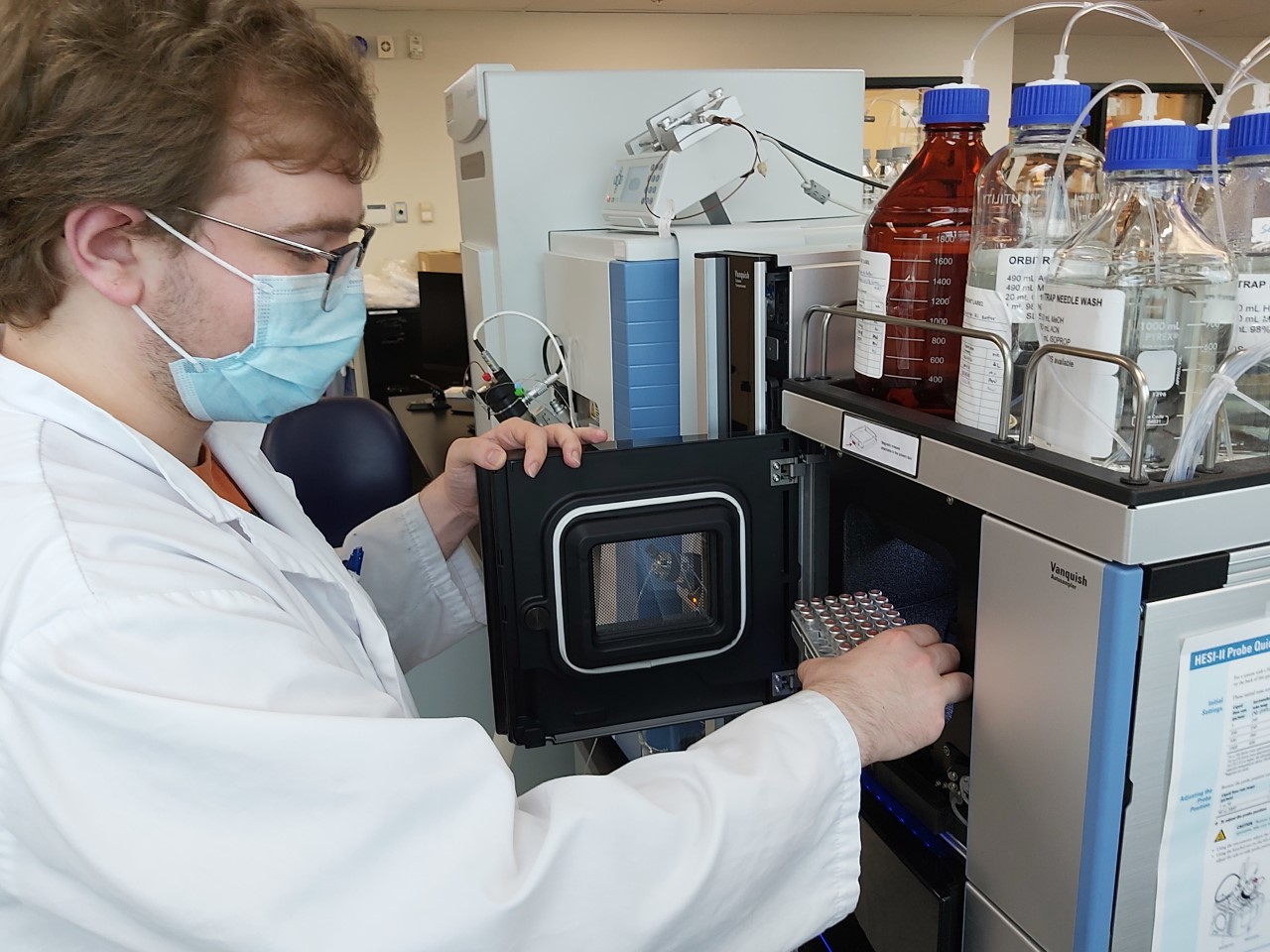 Young man removes lab test tubes from a device