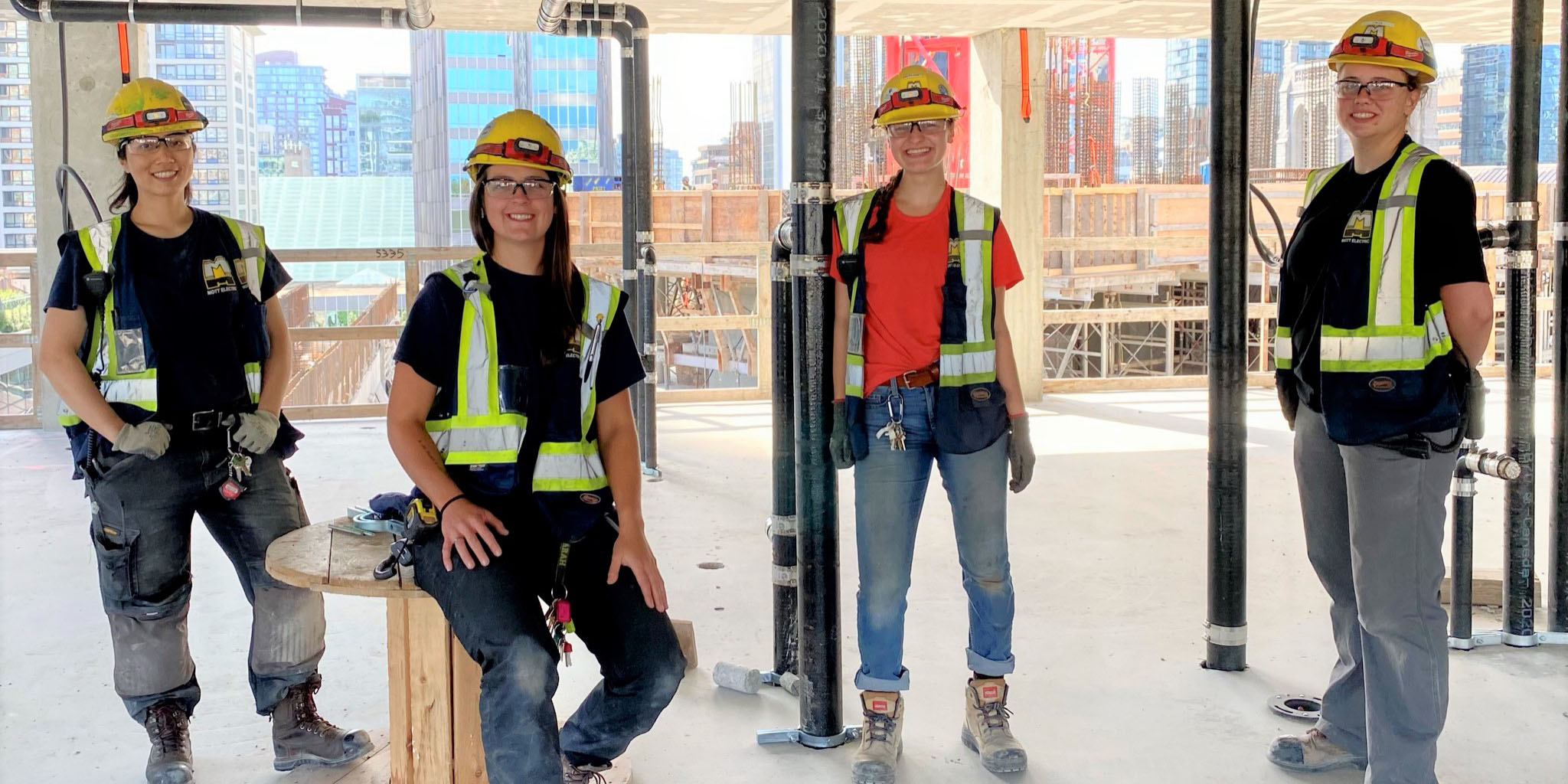 Four female electricians standing social distanced on their job site.